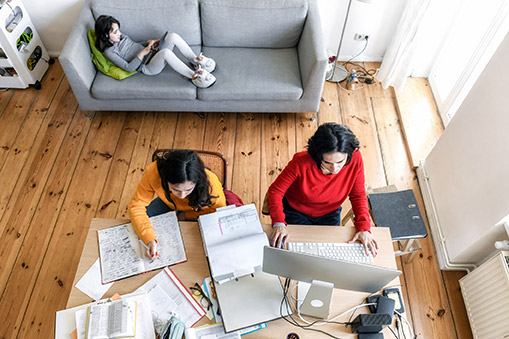 a mom and two girls working in a New York City appartment