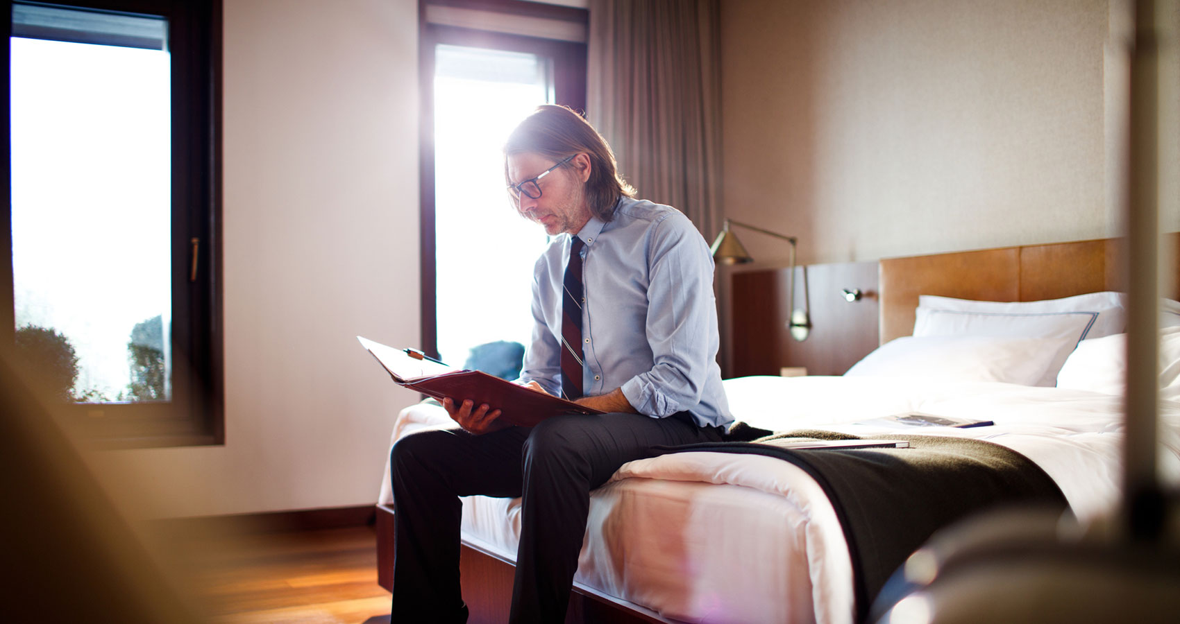 a man reads a book alone in a hotel room