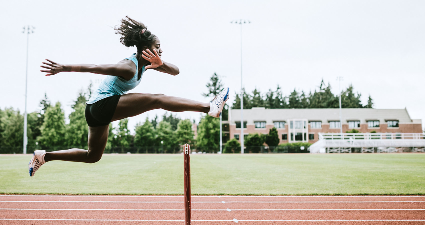 a woman jumps over a hurdle on a track